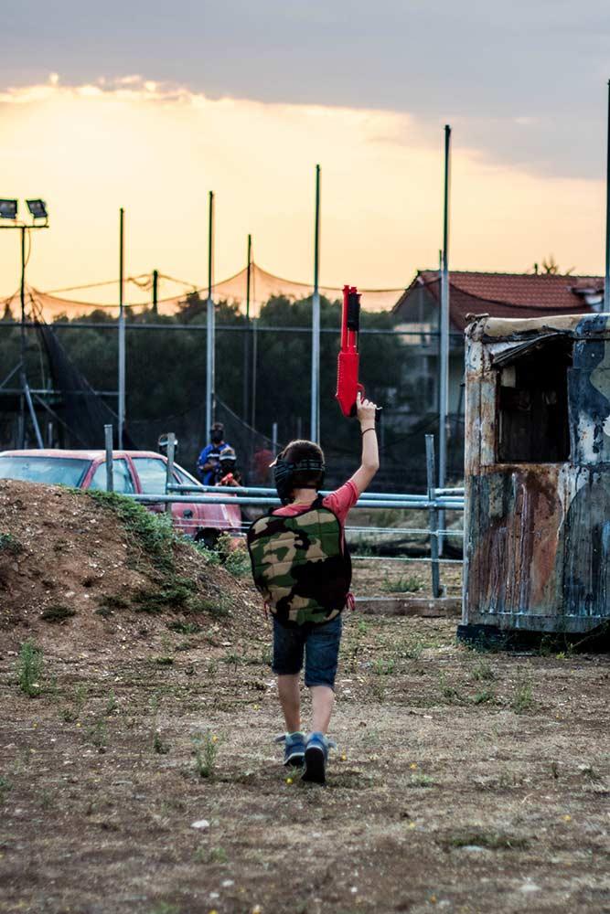 Paintball για παιδιά. Ένα παιδί κρατάει ψηλά το μαρκαδόρο paintball βγαίνοντας από το παιχνίδι