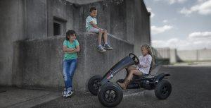 Κοριτσάκι πάνω σε μαύρο πεταλοκίνητο Go Kart και δύο αγόρια στο πλάι κοιτάν
