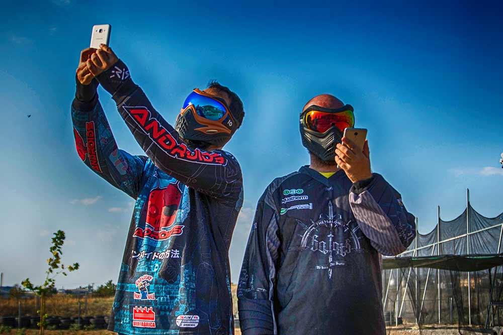 Δύο παίκτες Paintball με κινητό. Ο ένας ψάχνει σήμα, ο άλλος κοιτάει το κινητό