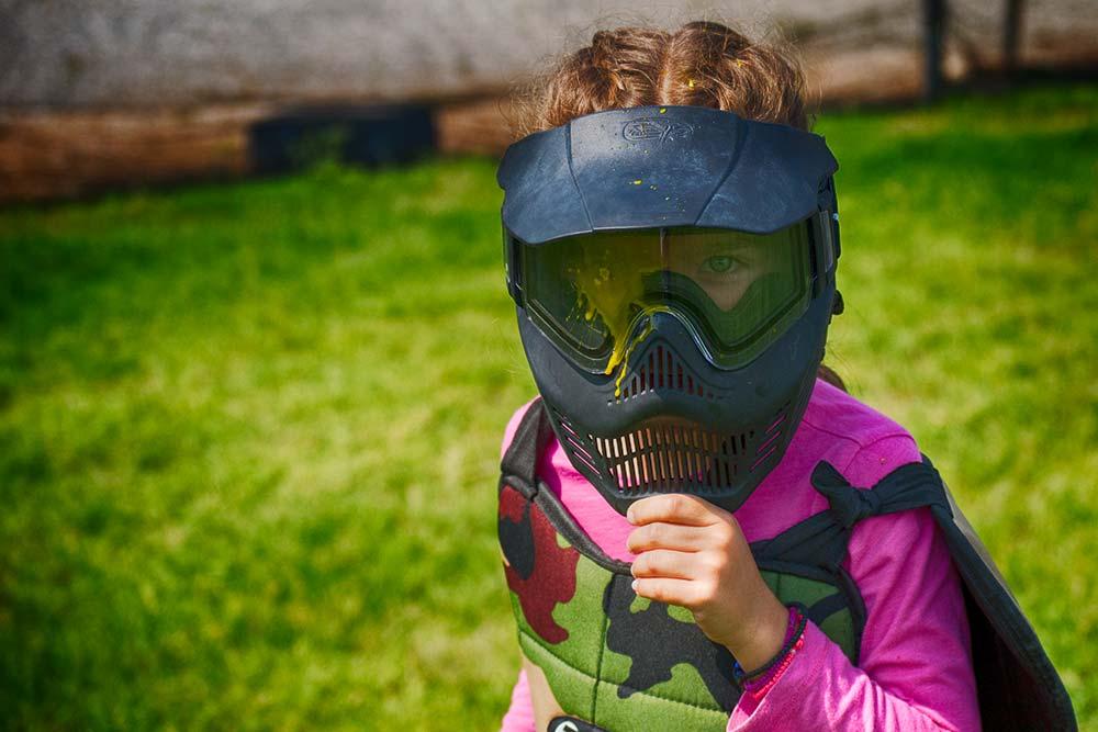 Ένα κοριτσάκι κοιτάει το φακό έχοντας δεχτεί χτύπημα επάνω στη μάσκα του paintball που φοράει