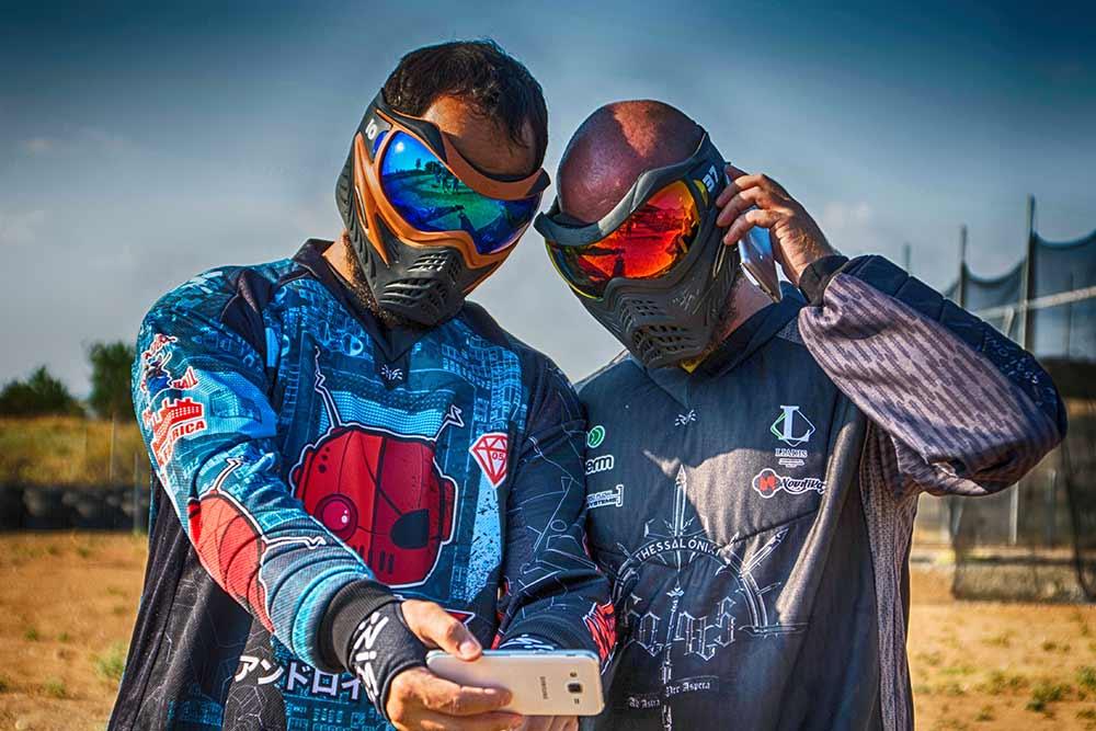 Δύο παίκτες Paintball με κινητό. Ο ένας μιλάει ο άλλος του δείχνει κάτι στο κινητό