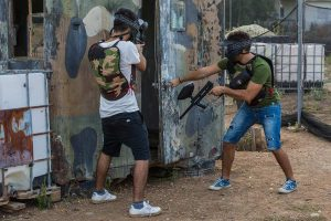 Two paintball players breaching a container